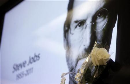 A flower is seen next to a portrait of Apple co-founder and former CEO Steve Jobs at Apple's store in Sao Paulo October 6, 2011. REUTERS/Nacho Doce