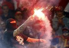 Болельщик сборной Сербии держит в руках фпйер на матче против команды Италии в Генуе 12 октября 2010 года. В пятницу, субботу и вторник пройдут последние матчи отборочного турнира к чемпионату Европы, который пройдет летом 2012 года на стадионах Украины и Польши. Ниже представлено их расписание. REUTERS/Alessandro Garofalo