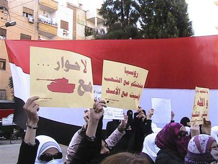 Demonstrators protesting against Syria's President Bashar al-Assad march through the streets in Homs, Syria, October 4, 2011. The signs read: ''No dialogue with tank'' (L) and ''Russia, your interests are with the people, not with Assad''.  REUTERS/Handout