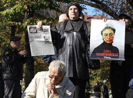A supporter of the ''Russia Without Lawlessness and Corruption'' opposition coalition holds a portrait of assassinated Russian journalist Anna Politkovskaya during a rally in Moscow October 9, 2010. REUTERS/Andrey Rudakov