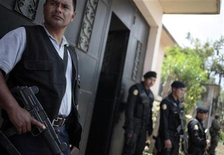 Police officers stand guard while others search a house in Coban, some 200 km (124 miles) northeast Guatemala City, September 9, 2011. REUTERS/Jorge Dan Lopez