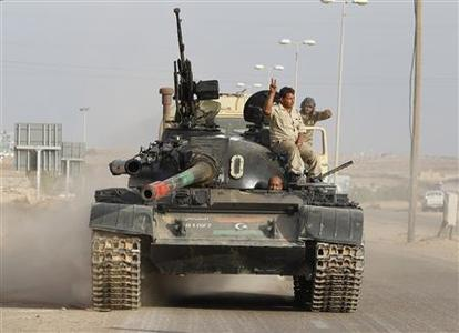 Members of Libya's government forces ride on a tank near Sirte, October 7, 2011. REUTERS/Saad Shalash