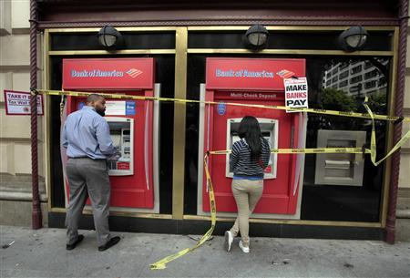 People use ATM machines at a Bank of America branch after it was occupied during a ''Make Wall Street Banks Pay'' protest march in Los Angeles, California October 6, 2011. REUTERS/Lucy Nicholson