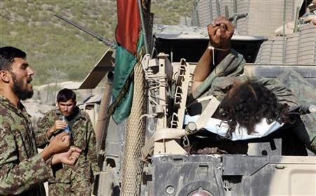 An Afghan soldier talks to a captured wounded Taliban fighter lying on a truck in Combat Outpost Pirtle King, in Kunar province, eastern Afghanistan September 27, 2011.   REUTERS/Erik De Castro