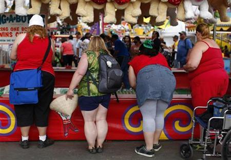 Fairgoers play a carnival game at the San Diego County Fair in Del Mar, California, June 29, 2011.   REUTERS/Mike Blake