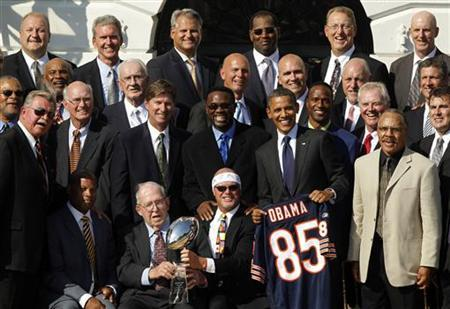 President Barack Obama holds a football jersey given to him by 1985 Chicago Bears coach Mike Ditka (front L) as defensive coordinator Buddy Ryan sits with the Superbowl trophy, as Obama honors the Super Bowl-winning Chicago Bears NFL team on the South Lawn of the White House in Washington October 7, 2011. REUTERS/Jason Reed