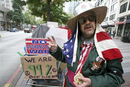 Garth Carroll, who calls himself Professor Gizmo, wears the American flag as he demonstrates at Occupy Seattle at Westlake Park in downtown Seattle, October 6, 2011. REUTERS/Marcus Donner