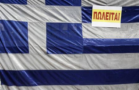 A Greek flag with a ''for sale'' sign is placed outside of the Interior Ministry during a blockade by employees in Athens September 29, 2011. REUTERS/John Kolesidis