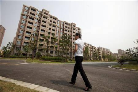 A real estate agent walks next to empty apartments at a new residential area in Shanghai September 8, 2011. REUTERS/Carlos Barria/Files