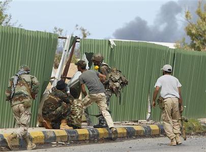 Anti-Gaddafi fighters take cover from incoming sniper fire as they push forward towards the centre of Sirte, October 9, 2011. REUTERS/Saad Shalash