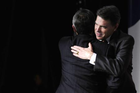 Republican U.S. presidential candidate Governor Rick Perry (R-TX) (R) hugs his presenter, pastor Robert Jeffress, as he takes the stage to address the Family Research Council's Values Voters Summit in Washington, October 7, 2011.  REUTERS/Jonathan Ernst
