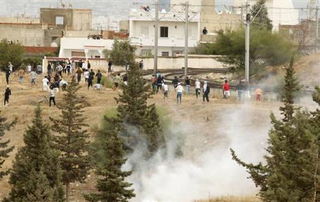 Protesters run for cover during riots in front of the main university campus in Tunis October 9, 2011. REUTERS/Zoubeir Souissi