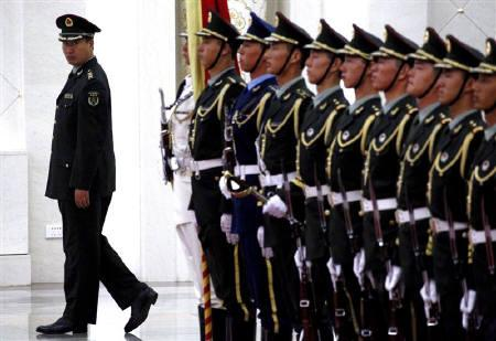 An officer checks the alignment of an honour guard before the start of a welcoming ceremony inside the Great Hall of the People in Beijing August 10, 2011. REUTERS/David Gray/Files