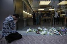 Поклонник Apple молится перед магазином компании в Токио, 6 октября 2011 года. Samsung Electronics Co решила отложить выпуск своих новых смартфонов на базе последней версии ОС Android от Google, пока весь мир отдает дань памяти основателю и вдохновителю Apple Стиву Джобсу, который умер на прошлой неделе. REUTERS/Yuriko Nakao