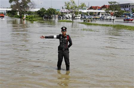 A policeman directs traffic in a flooded area in Ayutthaya province October 10, 2011. REUTERS/Sukree Sukplang