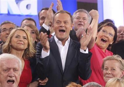 Poland's Prime Minister Donald Tusk (C) claps his hands after the election results announcement in Warsaw October 9, 2011.   REUTERS/Wojciech Olkusnik/Agencja Gazeta