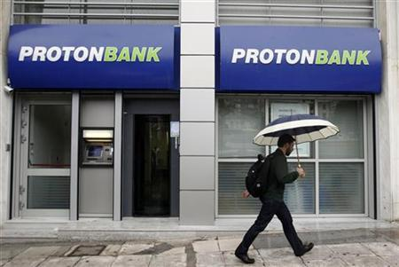 A man walks in front of a branch of Proton Bank in central Athens October 10, 2011. Greece's central bank said on Monday it activated a bank rescue fund to save Proton Bank, effectively nationalising the small lender that is under investigation for possible violation of the country's money-laundering laws.     REUTERS/Yiorgos Karahalis