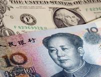 Банкноты номиналом 1 доллар и 10 юаней, Варшава, 26 января 2011 года. Юань завершил торги понедельника на рекордном максимуме закрытия против доллара, показав лучший дневной рост и прибавив более 30 процентов к американской валюте с его знаковой переоценки в июле 2005 года. REUTERS/Kacper Pempel