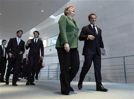 French President Nicolas Sarkozy (R) and German Chancellor Angela Merkel (C)  arrive to address a news conference at the Chancellery in Berlin October 9, 2011.  REUTERS/Fabrizio Bensch