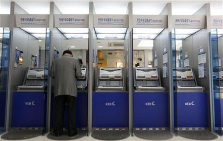 A customer uses an automated teller machine at the headquarters of the Korea Exchange Bank in Seoul October 6, 2011. REUTERS/Jo Yong-Hak