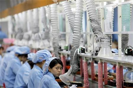 An employee looks up while working along a production line in Suzhou Etron Electronics Co. Ltd's factory in Suzhou, Jiangsu province in this June 8, 2010 file photo.  REUTERS/Aly Song