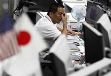 Трейдер работает в торговом зале Токийской фондовой биржи, 28 июля 2011 года. Фондовые рынки Азии выросли по итогам торгов во вторник благодаря решению Китая поддержать свои крупнейшие банки и обещаниям Германии и Франции найти выход из долгового кризиса еврозоны. REUTERS/Yuriko Nakao