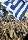 Демонстранты размахивают флагом Греции у здания парламента в Афинах 15 июня 2011 года. Греция может получить очередной транш кредитов в 8 миллиардов евро в начале ноября, сказали во вторник инспекторы Евросоюза, Международного валютного фонда и Европейского центрального банка по завершении двухнедельной оценки финансов страны. REUTERS/John Kolesidis