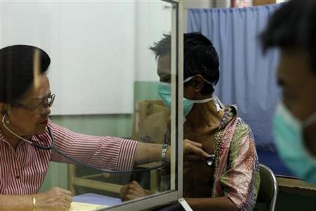 Doctor Marion Aritonang (L) checks the lungs of a newly diagnosed tuberculosis patient at the Indonesian Union Against Tuberculosis clinic in Jakarta, April 4, 2011.  REUTERS/Beawiharta