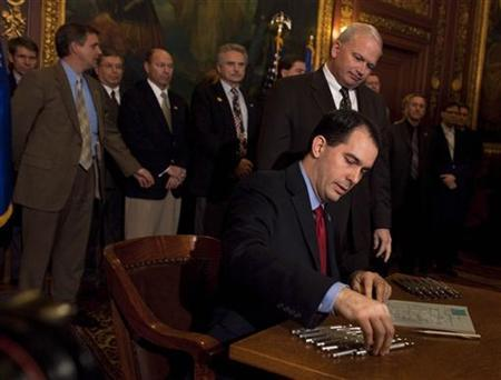 Wisconsin State Governor Scott Walker signs the ceremonial bill, after the Republican controlled House and Senate, eliminated almost all collective bargaining for most public workers at the state Capitol in Madison Wisconsin March 11, 2011. REUTERS/Darren Hauck