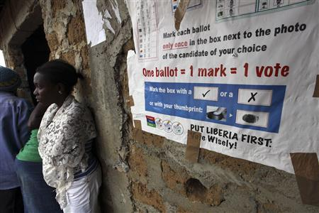 A woman stands next to an electoral banner at a polling station during the presidential election in Feefee in Bomi county October 11, 2011. REUTERS/Luc Gnago