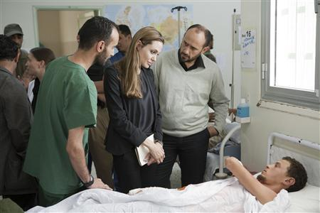 Actress and U.N. goodwill ambassador Angelina Jolie (C) visits a patient in a hospital in Misrata during her Libya visit  October 11, 2011.  REUTERS/Jason Tanner/Handout