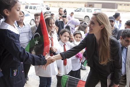 Actress and U.N. goodwill ambassador Angelina Jolie (R) greets a girl during a visit to Misrata October 11, 2011. REUTERS/Jason Tanner/Handout