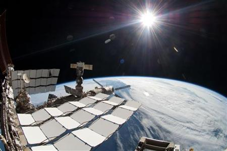 The sun, a portion of the International Space Station and Earth's horizon are seen during the Space Shuttle Endeavour STS-134 mission's fourth spacewalk in this NASA handout photo dated May 2011. REUTERS/NASA/Handout