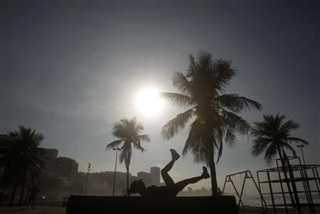 A woman exercises on Leblon beach in Rio de Janeiro August 25, 2011. REUTERS/Ricardo Moraes
