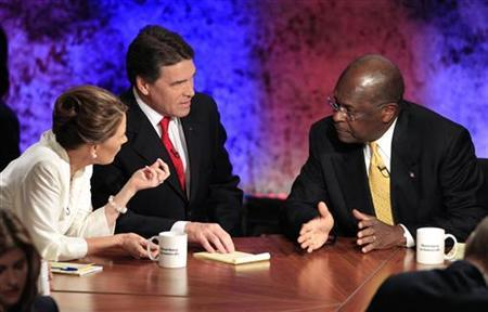 Republican presidential hopefuls Rep. Michele Bachmann (R-MN), Texas Gov. Rick Perry and businessman Herman Cain (R) talk during a break in their debate at Dartmouth College in Hanover, New Hampshire, October 11, 2011. REUTERS/Adam Hunger