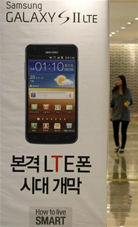 A woman walks past a billboard of Samsung Electronics' smart phone Galaxy S II LTE at the company's headquarters in Seoul October 7, 2011.   REUTERS/Jo Yong-Hak