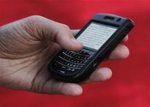 Мужчина читает сообщение с телефона Blackberry в Голливуде, 4 ноября 2010 года. Миллионы пользователей смартфонов BlackBerry по всему миру в среду снова остались без интернета, пока Research in Motion пытается исправить технические сбои у себя в сети.  REUTERS/Fred Prouser