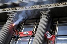Апологеты национал-большевистской партии размахивают флагами и выкрикивают лозунги, вломившись в здание Минфина в центре Москвы 25 сентября 2006. Пожар в среду в российском министерстве финансов, недавно лишившемся руководителя по воле Кремля, обошелся без пострадавших. REUTERS/Alexei Druzhinin