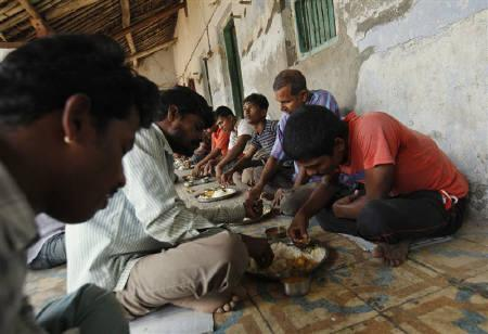 Unmarried men eat their lunch in the remote village of Siyani, where they also live and work in, about 140km (86 miles) west of Gujarat's capital Ahmedabad, October 5, 2011. REUTERS/Vivek Prakash