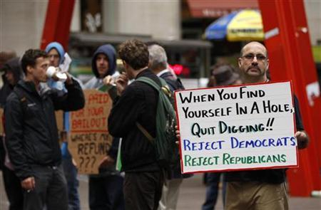 A member of the Occupy Wall St movement holds a sign as he demonstrates in Zuccotti Park near the financial district of New York October 12, 2011. REUTERS/Lucas Jackson