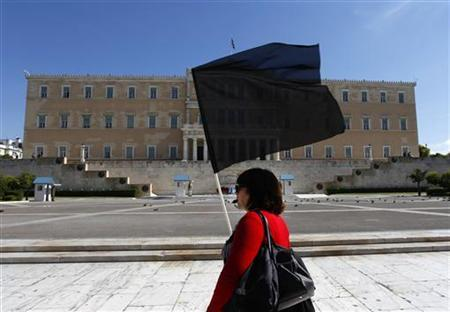 An employee of the Ministry of Labour blows a whisle and holds a black flag during a protest by public sector workers outside the Greek parliament in Athens October 12, 2011.  REUTERS/Yannis Behrakis