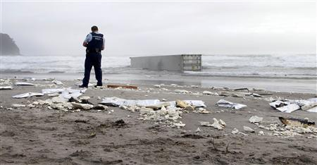 A policeman stands near debris and containers from the stricken container ship Rena, washed ashore at Mount Maunganui Beach October 13, 2011.  REUTERS/Sunlive/Handout