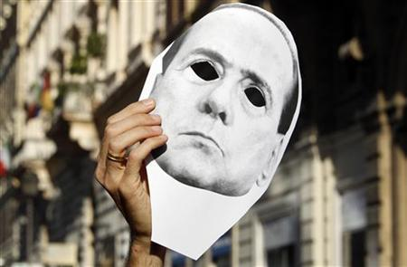 A demonstrator holds a mask of Italian Prime Minister Silvio Berlusconi's face during a sit-in protest near the Bank of Italy's headquarters in Rome October 12, 2011.  REUTERS/Stefano Rellandini
