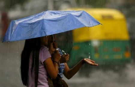 Women take shelter under an umbrella during monsoon showers in New Delhi July 12, 2007.  REUTERS/Vijay Mathur/Files
