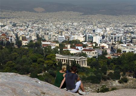 Tourists sit on a hill overlooking Athens outside the archaeological site of the Acropolis due to a 48-hour strike by Culture Ministry employees, October 13, 2011.  REUTERS/Yannis Behrakis