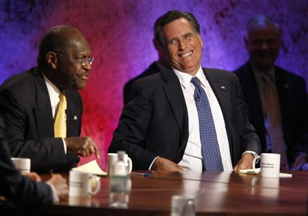 Republican presidential hopeful businessman Herman Cain speaks as former Massachusetts Governor Mitt Romney laughs at the Republican presidential debate at Dartmouth College in Hanover, New Hampshire, October 11, 2011. REUTERS/Scott Eells/Pool