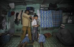 <p>Zameel, a 44-year-old migrant taxi driver, adjusts the tie of his son Salim, 8, as he prepares him for school inside their one room dwelling in a residential area in Mumbai October 7, 2011. REUTERS/Danish Siddiqui</p>