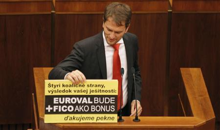 Member of Slovak Parliament Igor Matovic displays a banner during a repeated vote on the euro zone rescue fund, at the Slovak Parliament in Bratislava, October 13, 2011. The banner reads: ''Four coalition parties, result of your vanity: ESFS bailout fund will be + Fico will come as a bonus. Thank you very much''. REUTERS/Petr Josek