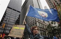 """Участница акции """"Оккупируй Уолл-стрит"""" держит флаг, протестуя в Zuccotti Park рядом с районом финансистов Нью-Йорка 12 октября 2011. Активисты акции """"Оккупируй Уолл- стрит"""" разъярены всё прирастающим богатством богачей на фоне падения доходов простых американцев. Однако возможно, что запалившая фитиль восстания организация опирается на средства одного из самых обеспеченных людей планеты. REUTERS/Lucas Jackson"""