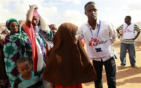 A Medecins Sans Frontieres (MSF) worker ushers newly arrived Somali refugees before they are administered polio vaccine at the Ifo extension refugee camp in Dadaab, near the Kenya-Somalia border August 1, 2011.  REUTERS/Thomas Mukoya